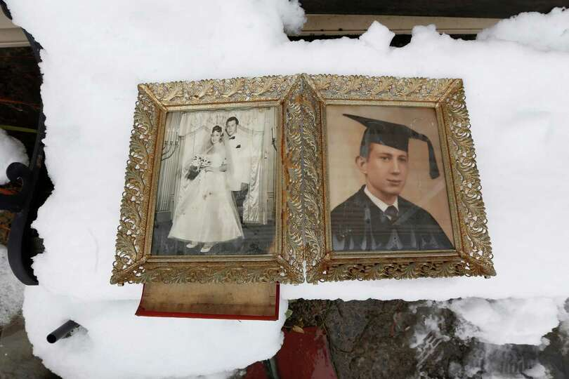 Photographs of Elliott Miller's wedding day and graduation lay on a snow covered bench as Jeanene Mi