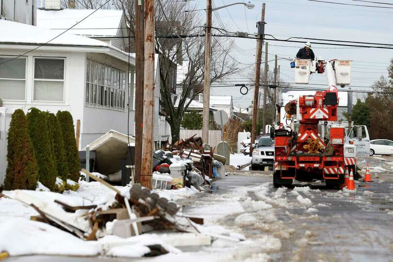 Utility workers check the power lines as snow covered debris from Superstorm Sandy lay on the side o