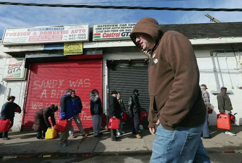 Residents wait on line to collect free gasoline the day after a Nor-Easter storm in the aftermath of