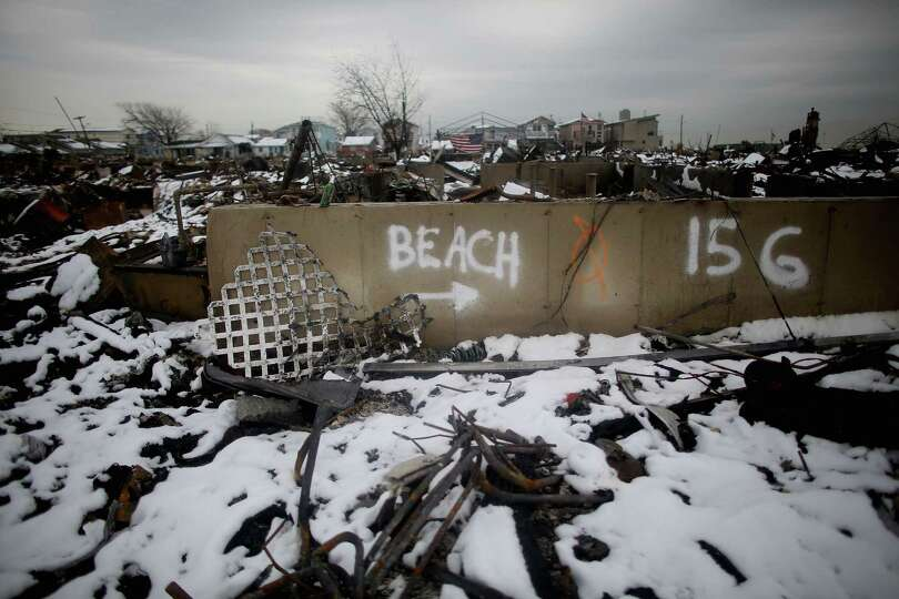 Snow from a Nor'Easter storm coats homes burned in the aftermath of Superstorm Sandy on November 8,
