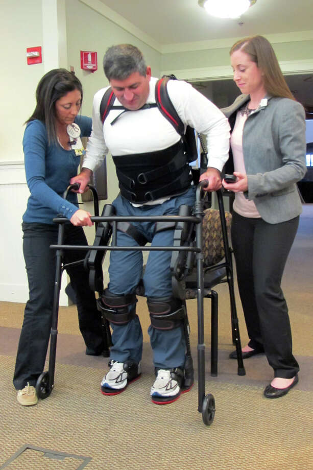Physical therapists Erin Prastine, left, and Erika Malits, right, help Mike Loura of Darien to his feet Thursday at Gaylord Specialty Healthcare in Wallingford. Loura, who has been paralyzed from the chest down since an accident in 2008, has been able to stand and walk with the help of Ekso, a robotic exoskeleton used to assist people lower-extremity paralysis or weakness. Gaylord is the only facility in Connecticut to have the device. Photo: Amanda Cuda / Connecticut Post