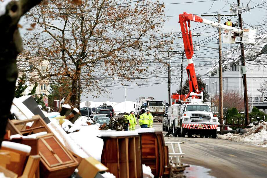 Utility workers the the power lines as snow covered debris from Superstorm Sandy lay on the side of a street following a nor'easter storm, Thursday, Nov. 8, 2012, in Point Pleasant, N.J.  The New York-New Jersey region woke up to wet snow and more power outages Thursday after the nor'easter pushed back efforts to recover from Superstorm Sandy, that left millions powerless and dozens dead last week. (AP Photo/Julio Cortez) Photo: Julio Cortez