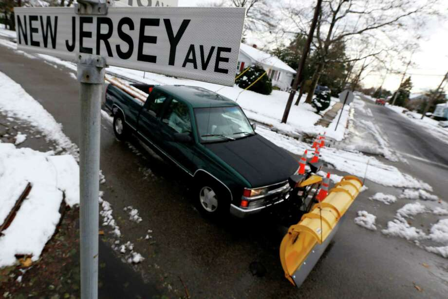 A snow plower drives on New Jersey Avenue as snow covered debris from  Superstorm Sandy lies on the sidewalk, Thursday, Nov. 8, 2012, in Point Pleasant, N.J.  A nor'easter hit the New Jersey shore on Wednesday, pounding the region which was already hit by Superstorm Sandy. (AP Photo/Julio Cortez) Photo: Julio Cortez