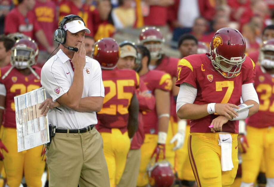 FILE - In this Oct. 20, 2012, file photo, Southern California head coach Lane Kiffin, left, looks on as quarterback Matt Barkley walks on to the field during the second half of an NCAA college football game against Colorado in Los Angeles.  A student manager's dismissal for underinflating game balls is just the latest embarrassment for USC. Coach Lane Kiffin says he and quarterback Matt Barkley knew nothing about this. But Kiffin's gamesmanship has been evident in other parts of the Trojans' season.  (AP Photo/Mark J. Terrill, File) Photo: Mark J. Terrill