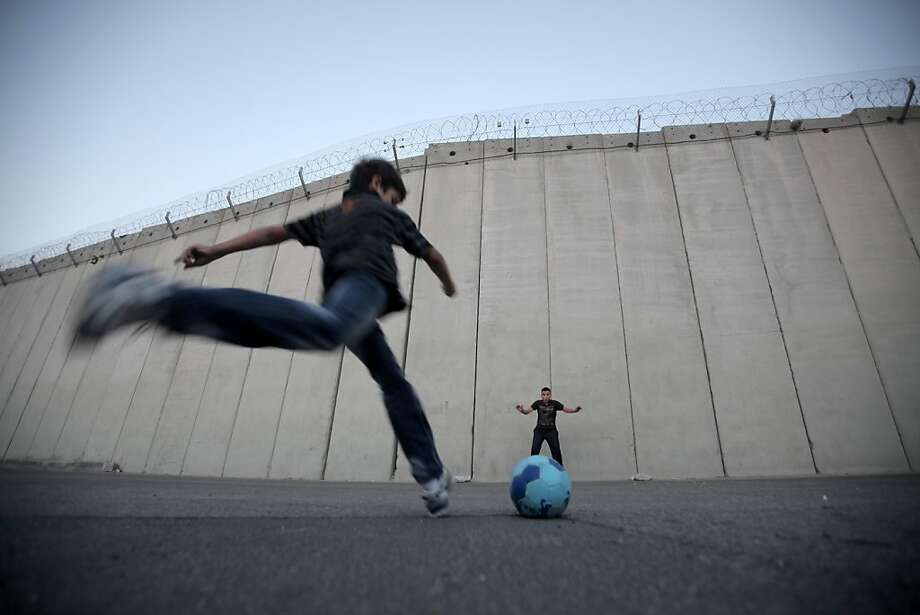 Palestinian children play football in front of the controversial Israeli separation barrier in the West Bank village of Abu Dis, on the outskirts of Jerusalem on November 8, 2012. Israeli and Palestinian leaders welcomed US President Barack Obama's re-election, but the two sides have very different hopes and expectations for his second term in office. Photo: Ahmad Gharabli, AFP/Getty Images