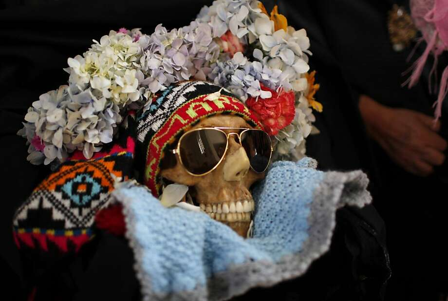 "A decorated human skull or Natita is carried out of the Cementerio General's chapel and to the Natitas Festival at the largest cemetery in La Paz, Bolivia, Thursday, Nov. 8, 2012. ""Natitas,"" are human skulls from unnamed, abandoned graves that are cared for and decorated by faithful who use them as amulets believing they serve as protection from thieves. The festival is a mixture of Andean ancestral worship rites and Catholic beliefs. According to experts, it was common practice in the pre-Hispanic era to keep skulls as trophies and display them during the rituals to symbolize death and rebirth. The festival marks the end of the All Saints' holiday, but is not recognized by the Catholic church. Photo: Juan Karita, Associated Press"