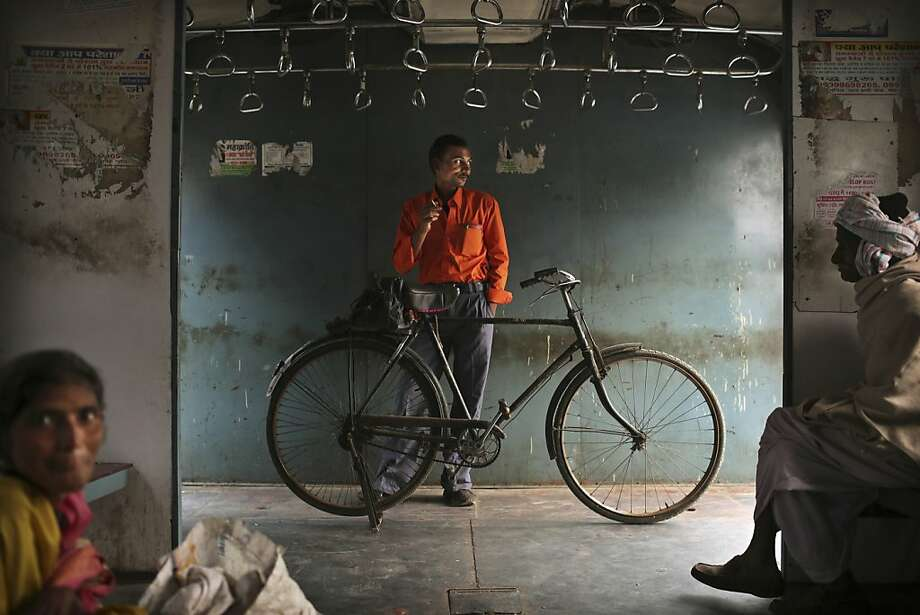 An Indian man smokes a cigarette as he stands with his bike on a local train in New Delhi, India, Thursday, Nov. 8, 2012. Photo: Kevin Frayer, Associated Press