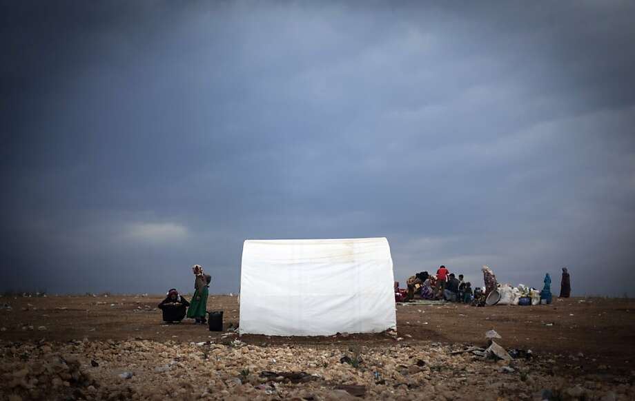 Syrian families who fled from the violence in their villages, sit next to their belongings at a displaced camp, in the Syrian village of Atmeh, near the Turkish border with Syria,Thursday, Nov. 8, 2012. Photo: Khalil Hamra, Associated Press