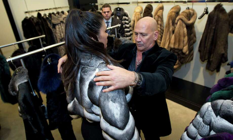 Designer Carmen Marc Valvo right, adjust a fur on a model during the Houston Chronicle's Style launch party at Saks Fifth Avenue Galleria Thursday, Nov. 8, 2012, in Houston.   
