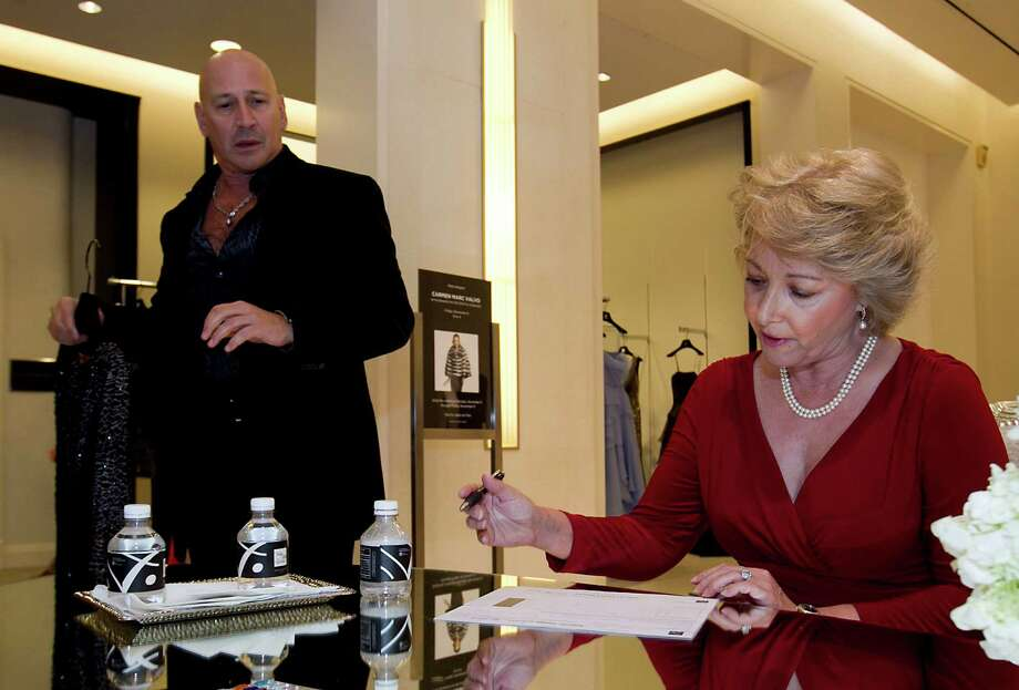 Designer Carmen Marc Valvo left, assist the Nutcracker raffle winner Catherine Sessums during the Houston Chronicle's Style launch party at Saks Fifth Avenue Galleria Thursday, Nov. 8, 2012, in Houston.   