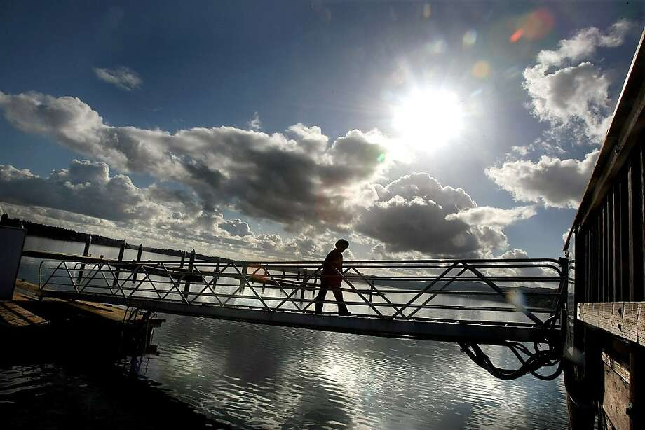 Rebecca Clauson of Silverdale walks up the ramp after taking a lunch time walk on the boat dock at Silverdale Waterfront Park, as the sun came out on Wednesday, Nov. 7, 2012. Photo: Larry Steagall, Associated Press