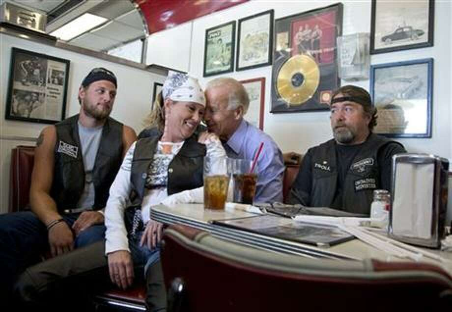 "As we'll see in photos to follow, the Happy Warrior likes to nuzzle. In this photo that went viral, the VP talks to customers during a stop at Cruisers Diner on Sept. 9 in Ohio. ""That's a picture of someone campaigning,"" Seth Myers deadpans on ""Saturday Night Live."" Jimmy Kimmel said, ""If he wins this thing, he's going to win it one unwanted back massage at a time."" (Carolyn Kaster / AP Photo)"