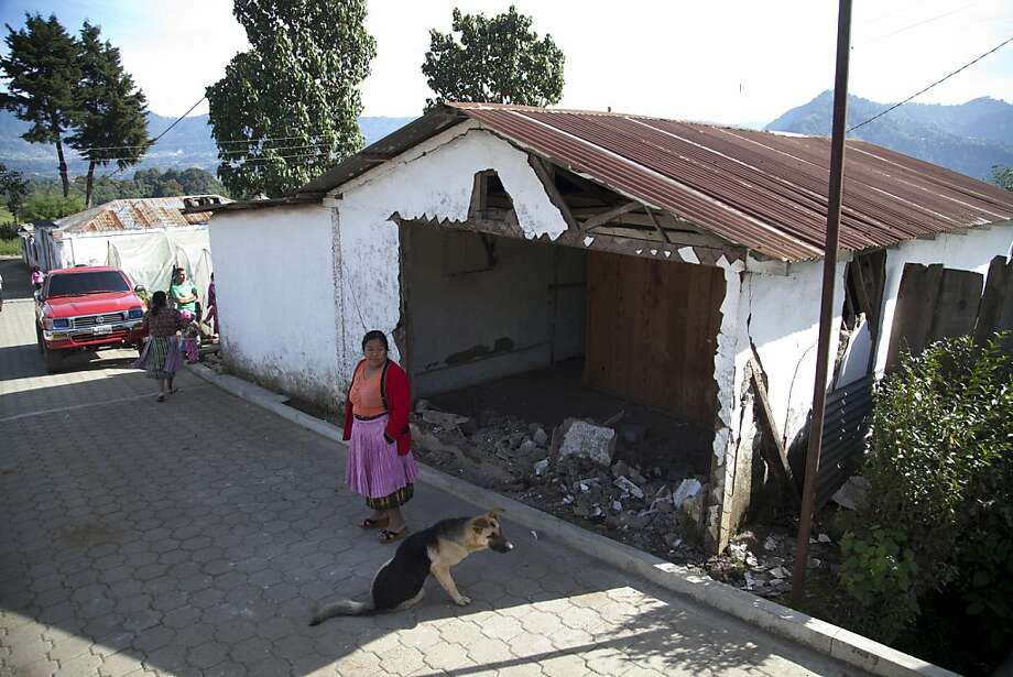 A resident stands outside a home that partially collapse during an earthquake, which authorities declared unsafe to live in, in San Cristobal Cucho, Guatemala, Thursday, Nov. 8, 2012. A magnitude 7.4 earthquake struck on Wednesday, killing at least 52 people and leaving dozens more missing. (AP Photo/Moises Castillo) Photo: Moises Castillo, Associated Press