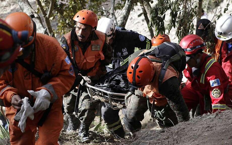 In this photo released by Guatemala's Presidential Press Office, rescue workers carry the body of a person who was killed during an earthquake in Barranca Grande, Guatemala, Thursday, Nov. 8, 2012. A magnitude 7.4 earthquake struck on Wednesday, killing at least 52 people and leaving dozens more missing. (AP Photo/Guatemala's Presidential Press Office, Edwin Bercian) Photo: Edwin Bercian, Associated Press
