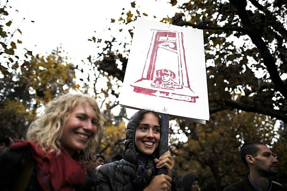 Grad student Meredith Palmer(R) holds a sign as she and Andrea Marston attend the walkout and rally at Sproul Plaza.  Berkeley and other UC campuses staged a walkout to push for using Prop 30 and other funds to immediately roll back tuition and cuts, on the Cal campus in Berkeley, CA, November 8th, 2012. Photo: Michael Short, Special To The Chronicle