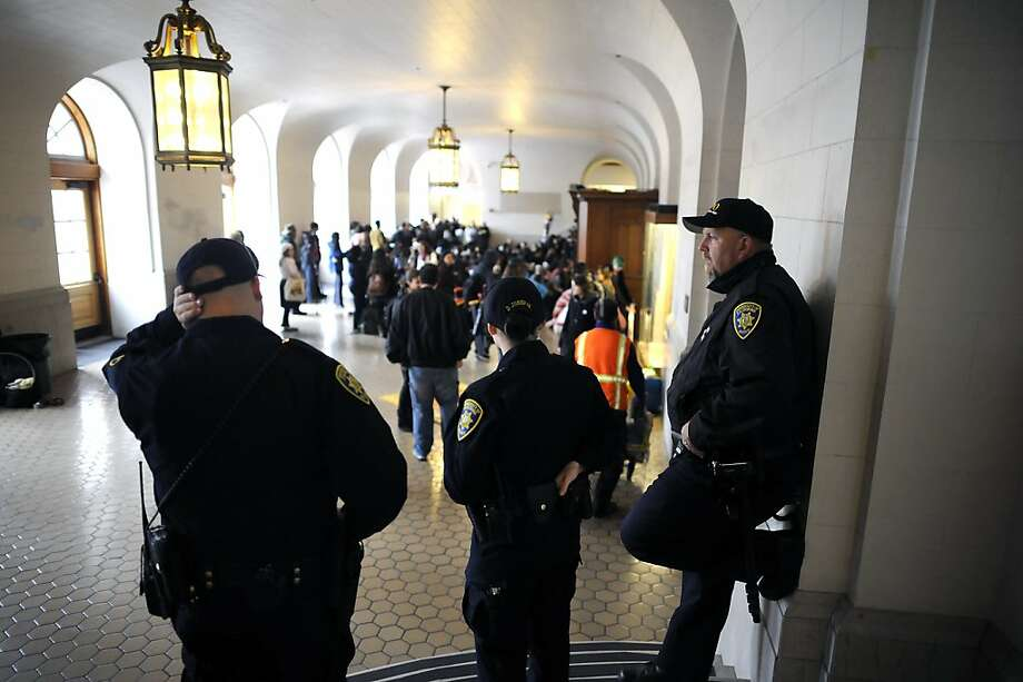 UC Police officers stand off to the side as they watch the gathering in Wheeler Hall.  Berkeley and other UC campuses staged a walkout to push for using Prop 30 and other funds to immediately roll back tuition and cuts, on the Cal campus in Berkeley, CA, November 8th, 2012. Photo: Michael Short, Special To The Chronicle