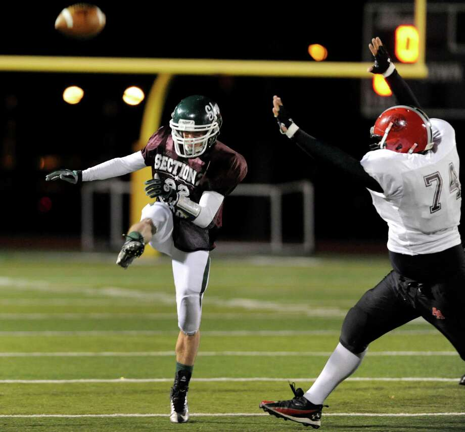 Shenendehowa's Corey Acker (22), center, punts the ball during the Section II Exceptional Senior Football game on Thursday, Nov. 8, 2012, at Shenendehowa High in Clifton Park, N.Y. Albany Academy's Alex Buchanan (74), right, puts on the pressure. (Cindy Schultz / Times Union) Photo: Cindy Schultz / 00020022A