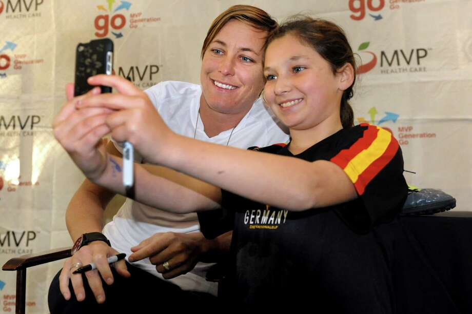 Alexandra O'Hara, 11, of Clifton Park, right, takes a picture with Abby Wambach, star of the U.S. women's national soccer team, on Thursday, Nov. 8, 2012, at Afrim's Sports Dome in Latham, N.Y. (Cindy Schultz / Times Union) Photo: Cindy Schultz / 00020020A