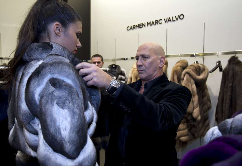 Designer Carmen Marc Valvo, right, adjusts a fur on a model during the Houston Chronicle's Style launch party