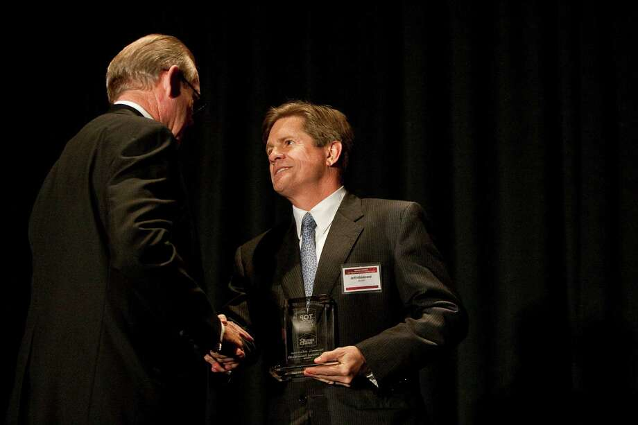 Houston Chronicle Chairman Jack Jack Sweeney, left, shakes hands with Hilcorp Energy Co. founder, Chairman, and CEO Jeffery Hildebrand, after Hildebrand won top leader for a medium employer during the Houston Chronicle's Top Workplaces Awards Gala, Thursday, Nov. 8, 2012, in Houston. Schiller also won leader of the year for small business. Photo: Nick De La Torre, Houston Chronicle / © 2012  Houston Chronicle