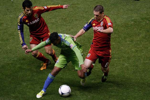 Real Salt Lake defender Tony Beltran (2) and Real Salt Lake midfielder Will Johnson (8) and Seattle Sounders FC midfielder Mario Martinez (15) during the first half of  an MLS playoff game  at Rio Tinto Stadium in Sandy, Utah, Thursday Nov. 8, 2012. Photo: AP