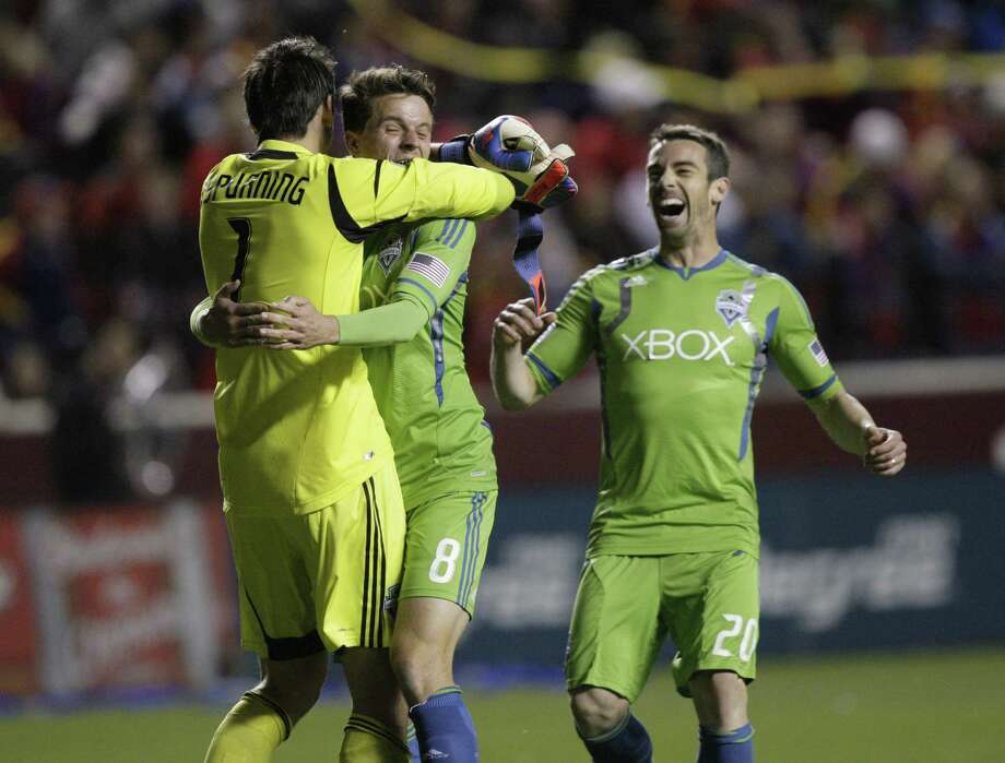 Seattle Sounders goalkeeper Michael Gspurning (1) receives a hug from teammate Marc Burch (8) as Zach Scott (20) looks on at the end of their MLS Western Conference semifinal soccer match with the Real Salt Lake Thursday, Nov. 8, 2012, in Sandy, Utah. The Sounders defeated Real Salt Lake.  The match, the second of a two-match aggregate game, ended with a score of 1-0  . Photo: AP