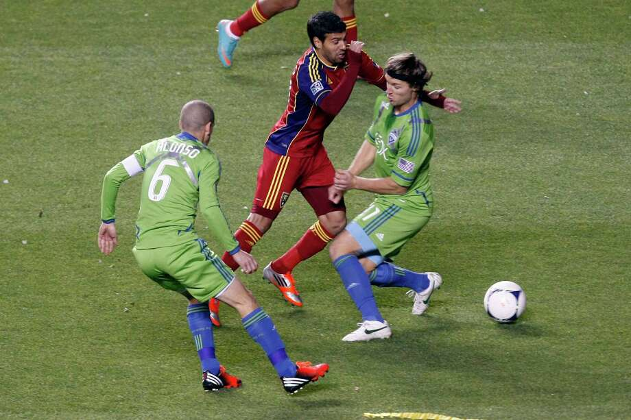 Real Salt Lake midfielder Javier Morales (11) runs around Seattle Sounders FC midfielder Osvaldo Alonso (6) and Seattle Sounders FC forward Fredy Montero (17) during the first half of  an MLS playoff game  at Rio Tinto Stadium in Sandy, Utah, Thursday Nov. 8, 2012. Photo: AP