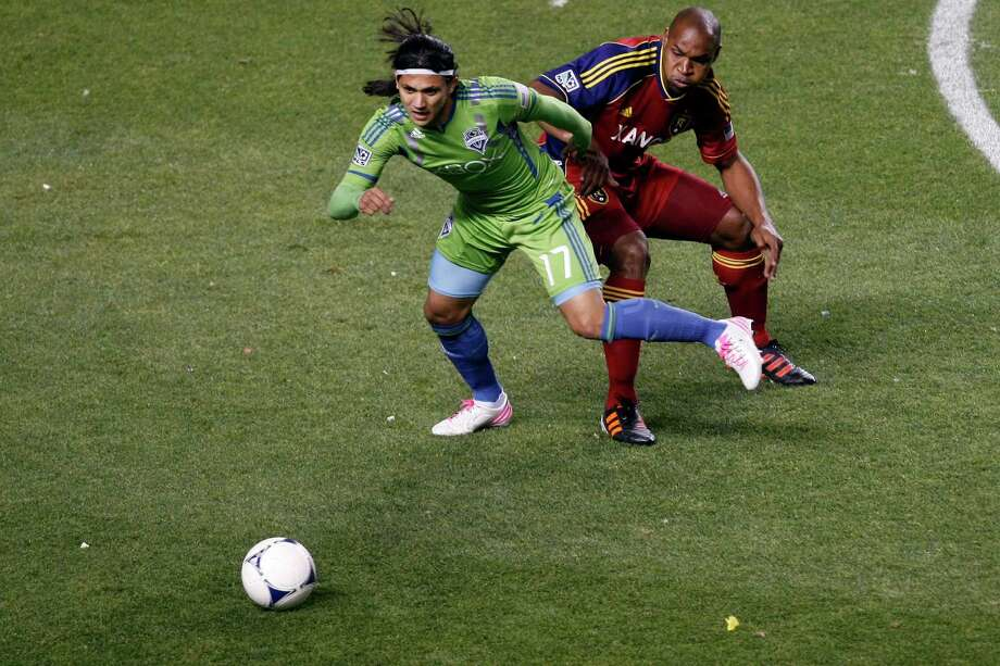 Real Salt Lake defender Jamison Olave (4) and Seattle Sounders FC forward Fredy Montero (17) during the first half of the Major League Soccer playoff game at Rio Tinto Stadium in Sandy, Utah, Thursday Nov. 8, 2012. Photo: AP