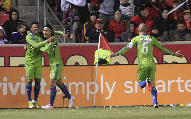 Seattle Sounders Mario Martinez, left, celebrates with teammates Fredy Montero, center, David Estrada (16) in the second half during an MLS Western Conference semifinal soccer match with Real Salt Lake Thursday, Nov. 8, 2012, in Sandy, Utah. The Sounders defeated Real Salt Lake. The match, the second of a two-match aggregate game, ended with a score of 1-0. Photo: AP