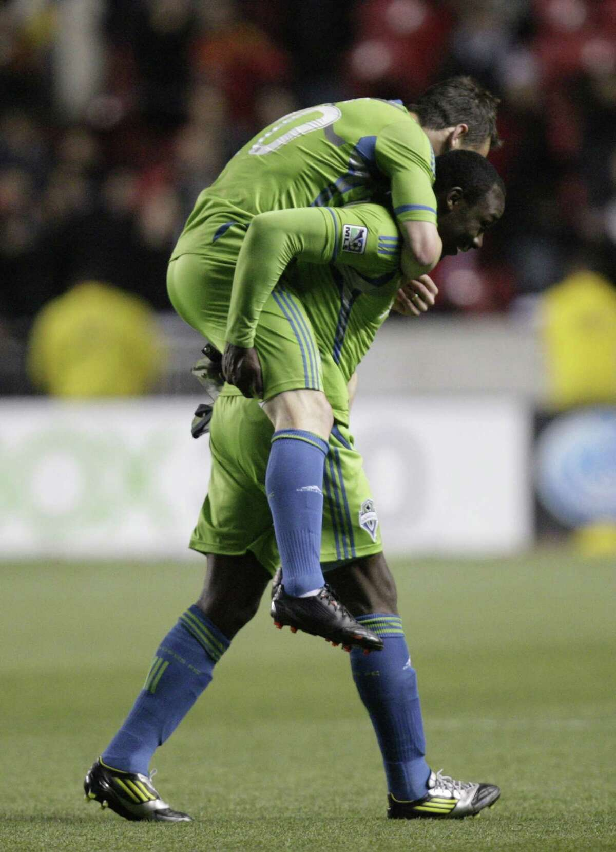 Seattle Sounders defender Zach Scott rides the back of teammate Seattle Sounders defender Jhon Kennedy Hurtado (34) following their MLS Western Conference semifinal soccer match with Real Salt Lake Thursday, Nov. 8, 2012, in Sandy, Utah. The Sounders defeated Real Salt Lake. The match, the second of a two-match aggregate game, ended with a score of 1-0.