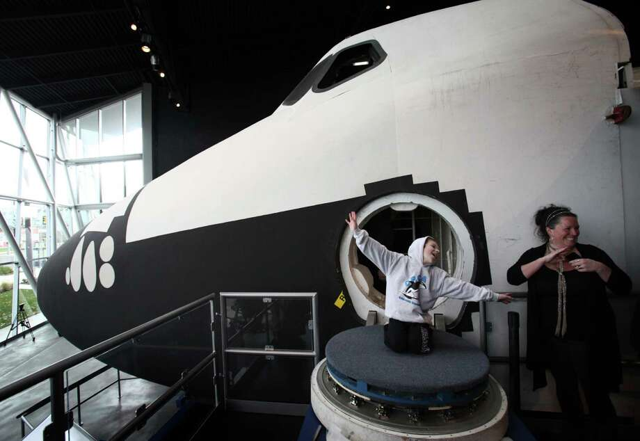 Sam Smith, 9, emerges from the crew compartment of the Space Shuttle Full Fuselage Trainer on Thursday, November 8, 2012 in the Charles Simonyi Space Gallery at Seattle's Museum of Flight. The Museum will host a public grand opening event for the new exhibit on Saturday, November 10th. The fully-assembled shuttle trainer is four storeis tall and over 100 feet long and was used to train every space shuttle astronaut. Photo: JOSHUA TRUJILLO / SEATTLEPI.COM