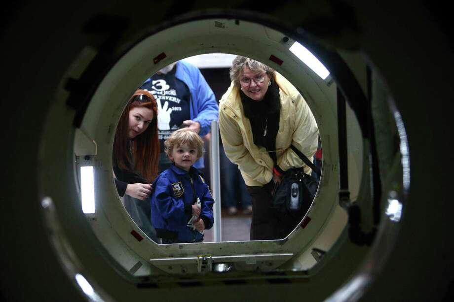 Visitors look into an air lock chamber on the Space Shuttle Full Fuselage Trainer on Thursday, November 8, 2012 in the Charles Simonyi Space Gallery at Seattle's Museum of Flight. The Museum will host a public grand opening event for the new exhibit on Saturday, November 10th. The fully-assembled shuttle trainer is four storeis tall and over 100 feet long and was used to train every space shuttle astronaut. Photo: JOSHUA TRUJILLO / SEATTLEPI.COM