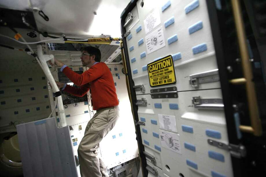 Exhibit developer Geoffrey Nunn climbs onto the flight deck of the Space Shuttle Full Fuselage Trainer on Thursday, November 8, 2012 in the Charles Simonyi Space Gallery at Seattle's Museum of Flight. The Museum will host a public grand opening event for the new exhibit on Saturday, November 10th. The fully-assembled shuttle trainer is four storeis tall and over 100 feet long and was used to train every space shuttle astronaut. Photo: JOSHUA TRUJILLO / SEATTLEPI.COM