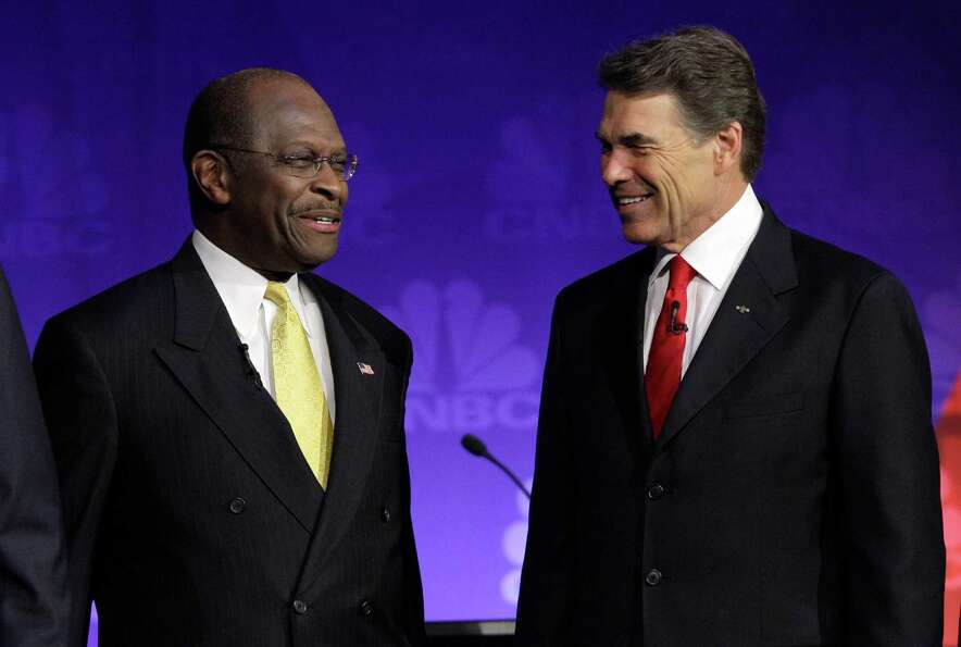 Herman Cain and Rick Perry talk before a Republican presidential debate at Oakland University in Aub
