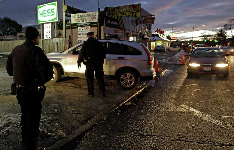 Police officers help keep order at a Hess gas station in the Brooklyn borough of New York where gas is still scarce, Thursday, Nov. 8, 2012.  Fuel shortages and distribution delays that led to gas hoarding have prompted New York City and Long Island to initiate an even-odd gas rationing plan which begins Friday at 6 a.m. in New York and 5 a.m. in Long Island. The line at this station was about an hour and 40 minutes, according to drivers waiting for gas. (AP Photo/Kathy Willens) Photo: Kathy Willens