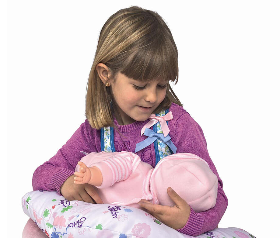 This product image released by Berjuan Toys shows  a girl playing with The Breast Milk Baby doll. The breastfeeding doll, whose suckling sounds are prompted by sensors sewn into a halter top, has caught some flak after hitting the U.S. market. (AP Photo/Berjuan Toys) Photo: HOEP / Berjuan Toys