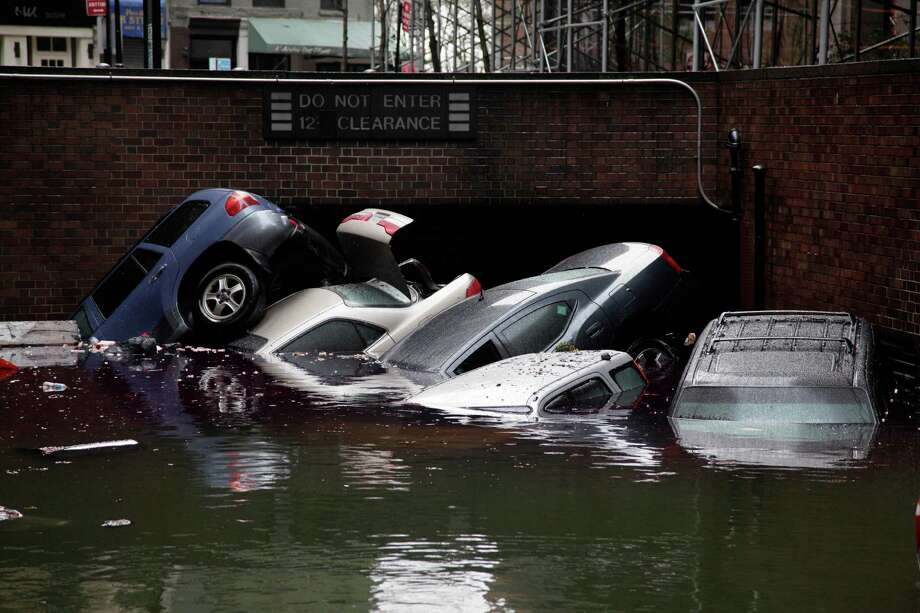 FILE -In this Tuesday, Oct. 30, 2012, file photo, cars are submerged at the entrance to a parking garage in New York's Financial District in the aftermath of superstorm Sandy. Alarming claims that hundreds of thousands of flood-damaged cars from Superstorm Sandy will inundate the used car market aren't backed up by insurance company claim data, The Associated Press has found. The dire predictions come mostly from companies that track vehicle title and repair histories and sell those reports.(AP Photo/Richard Drew) Photo: Richard Drew