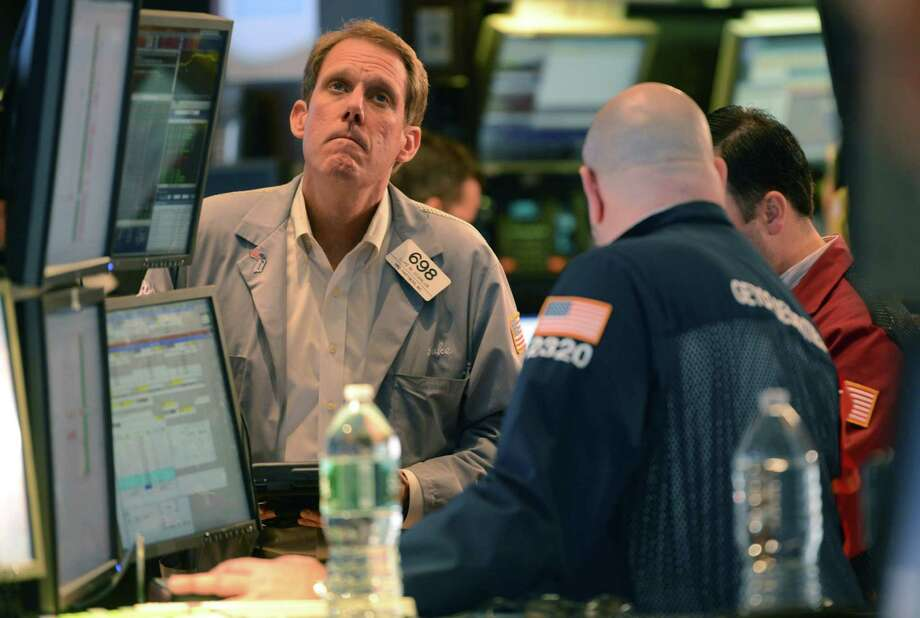 In this Wednesday, Nov. 7, 2012, photo, Luke Scanlon, left, of MND Partners Inc. works on the floor of the New York Stock Exchange in New York. Financial markets settled down Thursday, Nov. 8, 2012, after the turmoil of the previous day when concerns over the U.S. fiscal situation combined with renewed worries over the European economy to hammer stocks. (AP Photo/Henny Ray Abrams) Photo: Henny Ray Abrams