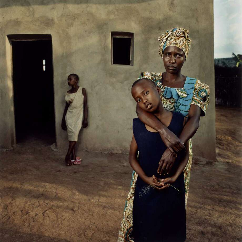 "From ""WAR/PHOTOGRAPHY"" at the Museum of Fine Arts, Houston:Jonathan C. Torgovnik, American (born 1969), Valentine with her daughters Amelie and Inez, Rwanda, from the series Intended Consequences, 2006, chromogenic print, ed. #11/25, the Museum of Fine Arts, Houston, gift of the artist.  Jonathan Torgovnik. This photo depicts a woman who was raped, then outcast from her village. The daughter in the background is the child of the rape; her father killed her sister's father. / © Jonathan Torgovnik"