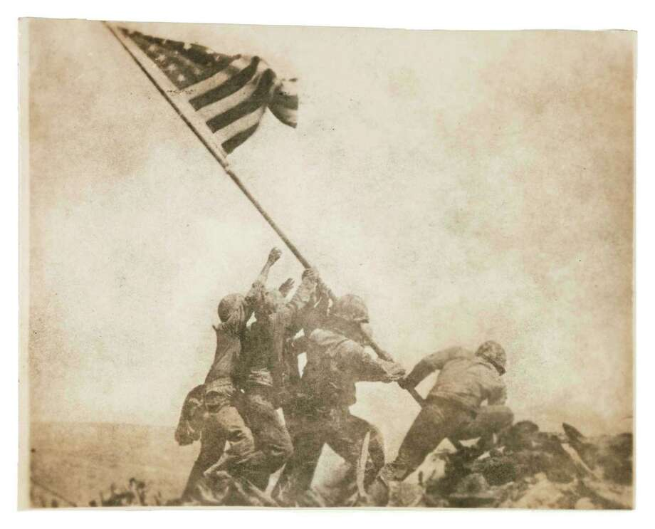 """From """"WAR/PHOTOGRAPHY"""" at the Museum of Fine Arts, Houston: MFAH curators Anne Tucker and Will Michaels began their 10-year quest to explore war photography when the museum was gifted with this first print of Joe Rosenthal's iconic """"Old Glory Goes Up on Mount Suribachi, Iwo Jima."""" Joe Rosenthal, American (1911-2006), Old Glory Goes Up on Mount Suribachi, Iwo Jima, February 23, 1945, gelatin silver print, the Museum of Fine Arts, Houston, gift of the Kevin and Lesley Lilly Family, The Manfred Heiting Collection.  Associated Press Photo: Joe Rosenthal / © Associated Press"""