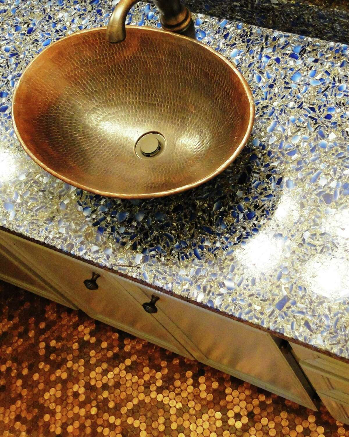 A hammered copper sink complements the floor of pennies in the bathroom floor of New Braunfels resident Doreen Fisher. Fisher placed the pennies --almost 10,000 of them -- and sealed them with epoxy. The Vetrazzo counter is made of recycled liquor bottles.