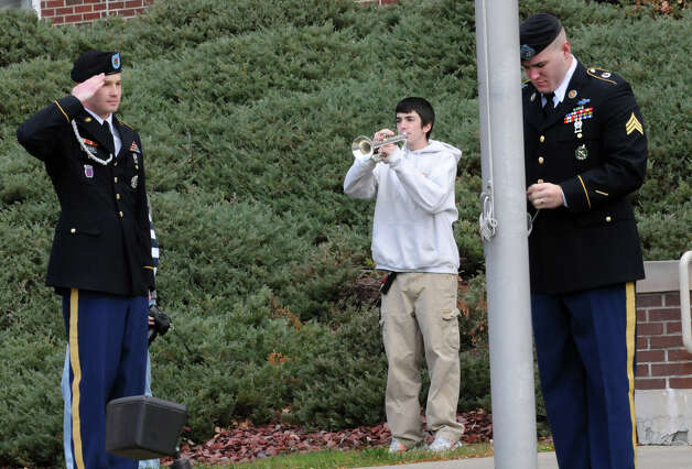 SCCC student Adam Flock, a Performing Arts: Music major, plays Taps as Schenectady County Community College honors veterans with a colors ceremony on Friday, Nov. 9, 2012, in Schenectady, N.Y. Army Sgt. Marshall Reeves salutes as Jeffrey Klein raises the flag to half-staff. SCCC was recently named to the Military Friendly Schools list by Victory Media, the premier media entity for military personnel transitioning into civilian life. (Lori Van Buren / Times Union) Photo: Lori Van Buren