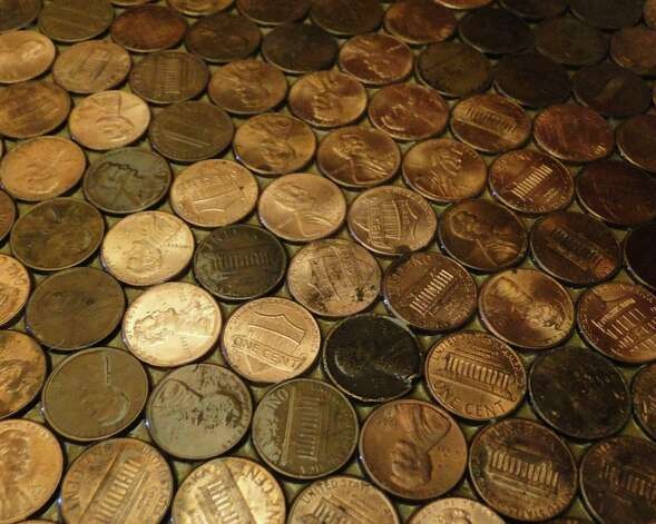Interesting shapes reveal themselves among the random pattern of pennies on the bathroom floor of a New Braunfels home. Homeowner Doreen Fisher Doreen Fisher placed almost 10,000 pennies on the floor and sealed them with epoxy. Photo: Tracy Hobson Lehmann