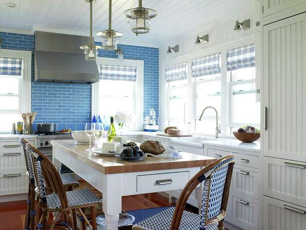 A blue backsplash of Veneto glass tiles covers an entire wall of this kitchen. Photo: House Beautiful