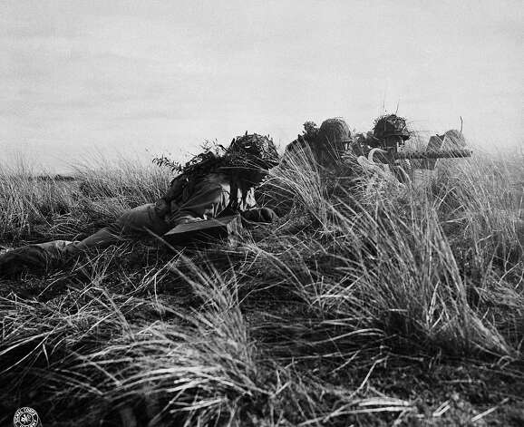 U. S.Soldiers undergoing invasion training in Britain are about to open up with their Machine Gun, May 5, 1944. Soldiers crawled several hundred yards while live fire from heavy weapons screamed over their heads. Photo: AP / 1944 AP