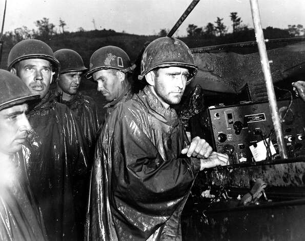 Fighting men of the U.S. Army's 77th Infantry Division on Ryukyu Island in Japan hear the news of Germany's surrender on May 8 a few yards behind the front lines during World War II. Photo: ASSOCIATED PRESS / AP1945