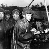 Fighting men of the U.S. Army's 77th Infantry Division on Ryukyu Island in Japan hear the news of Germany's surrender on May 8 a few yards behind the front lines during World War II.