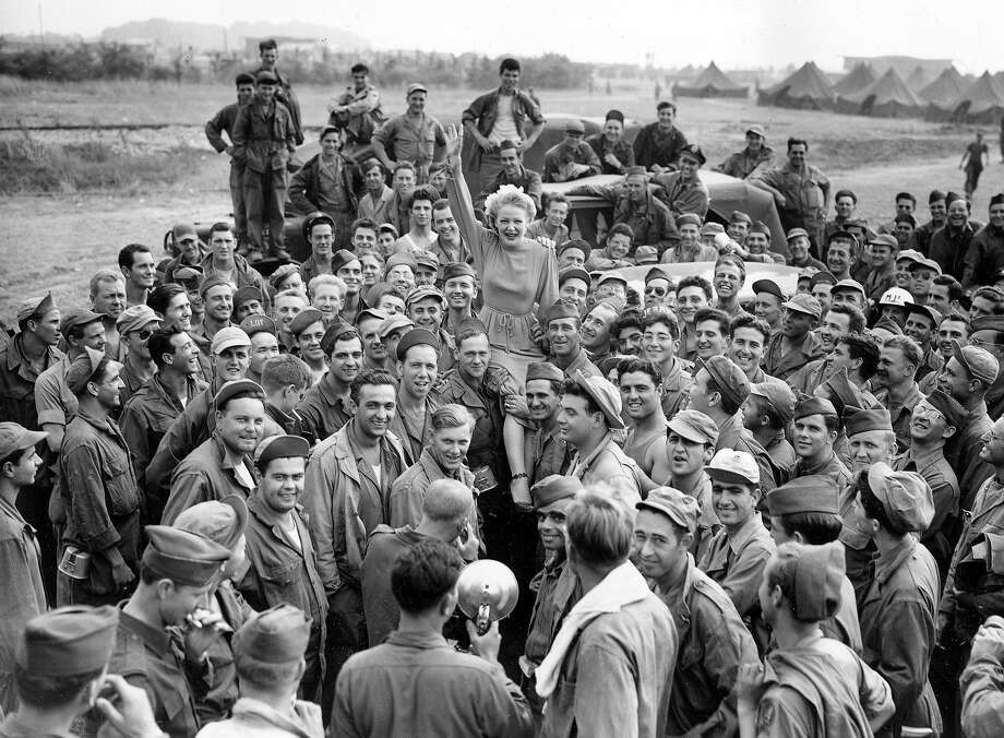 Blonde bombshell Betty Hutton is carried on some joyous G.I.'s shoulders, after her USO show at U.S. Army redeployment center Camp Detroit, at Reims, France, on August 14, 1945. Photo: HENRY L. GRIFFIN, ASSOCIATED PRESS / AP1945