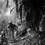 U.S. troops in the Pacific islands continued to find enemy holdouts long after the main Japanese forces had either surrendered or disappeared. Guam was considered cleared by August 12, 1944, but parts of the island were still dangerous half a year later. Here, patrolling Marines pass a dead Japanese sniper. These Marines may belong to the Fifty-second Defense Battalion, one of two black units sent to the Pacific.