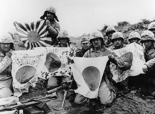 U.S. troops display captured Japanese flags during World War II. Photo: AP / AP1945